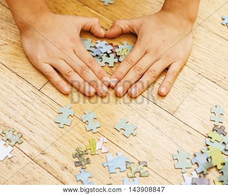 little kid playing with puzzles on wooden floor together with parent, lifestyle people concept, loving hands to each other, warm wooden interior close up