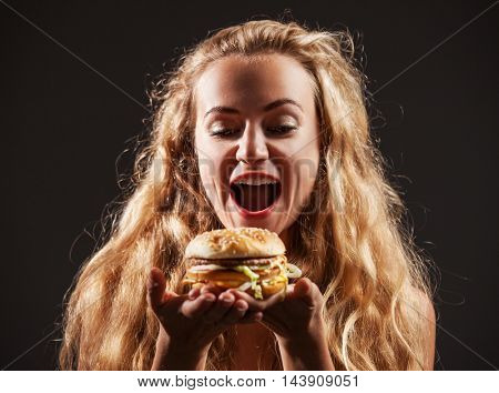 Female with hamburger. Woman eating unhealthy food