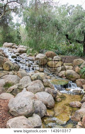 Man made trickling waterfall with rocks in garden feature with native plants at King's Park in Perth, Western Australia.