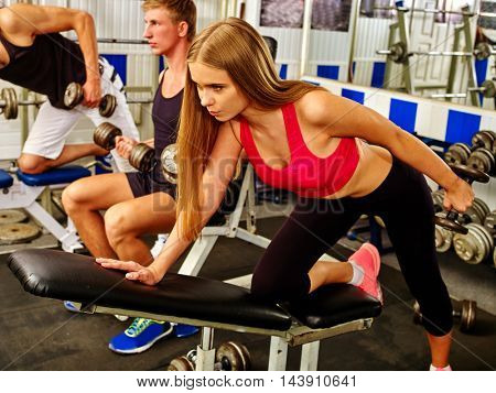 Group of people working with dumbbells his body at gym. Girl in red work with dumbbells on foreground.