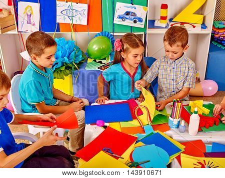 Large group children make from colored paper on table in school. Education of children in primary school. Top view of children and teacher.