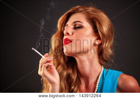 Portrait of girl who smokes cigarette. Smokes is bad habit.