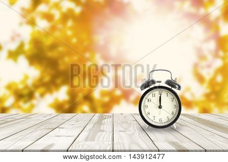 alarm clock on Wood table and Maple leaves blurred in background with sunlight. Abstract time.