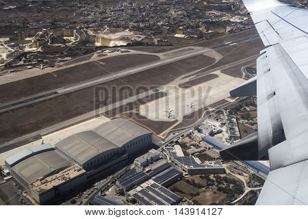 LUQA, MALTA - AUGUST 06 2016: Aerial view of Malta airport runway and buildings. Shot taken inside departing commercial aircraft.