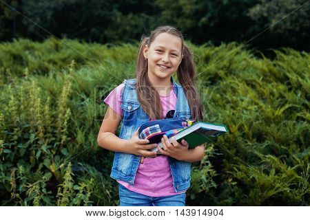 beautiful little girl standing in the yard with book and notebook