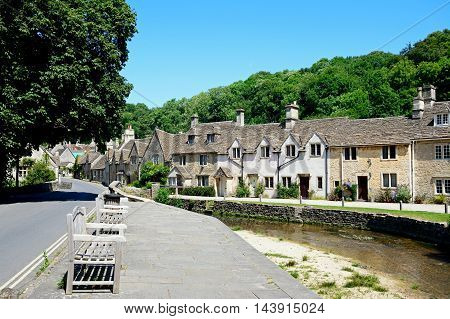Stone cottages alongside the river Bybrook with wooden benches in the foreground Castle Combe Wiltshire England UK Western Europe.
