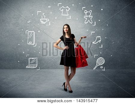 A beautiful young girl in black standing with red shopping bags in front of urban wall background and laptop, shoes, tennis icons concept
