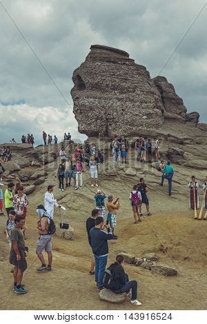 Bucegi Mountains Romania - August 6 2016: Thousands of people hike to Sphinx (Romanian: Sfinxul) the ancestral megalith with human face resemblance situated at 2216 m altitude in Bucegi Mountains.