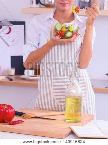 Woman eating fresh salad in modern kitchen