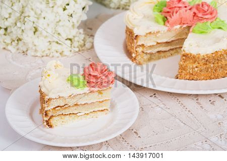 Creamy cake on plate on table on light background selective focus.