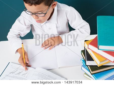 Pensive cute boy with homework sitting at a table blue background
