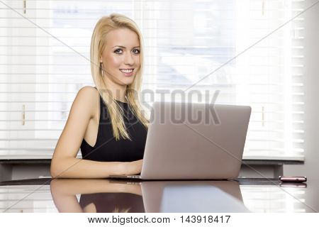 Portrait of a beauty young adult attractive business woman using laptop at office