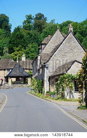 View along the main village street towards the fourteenth century market cross in the village centre Castle Combe Wiltshire England UK Western Europe.
