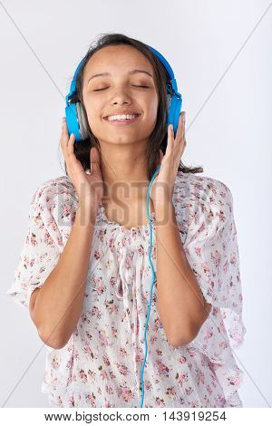 Mixed race woman with headphones listening to music and creating a playlist on her phone