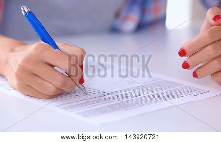 Beautiful young woman writing something in her note pad , isolated
