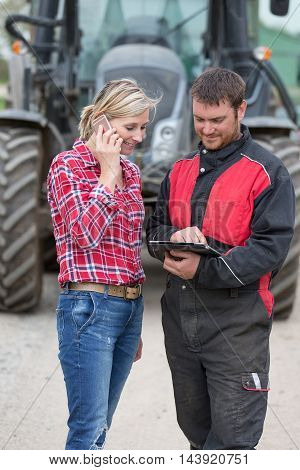Farmer and technician working together with electronics