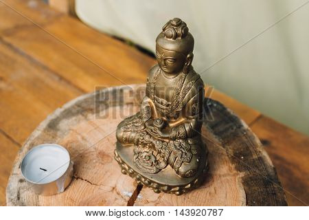 Gold plated Buddha statue standing on a wooden stand and candles in front of him