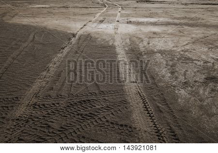 Wheel tracks on dirt road texture background