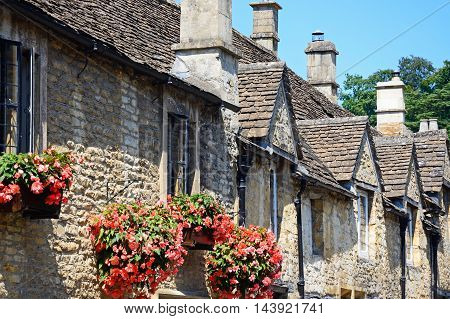 Cotswold stone cottages with pretty hanging baskets in the village centre Castle Combe Wiltshire England UK Western Europe.
