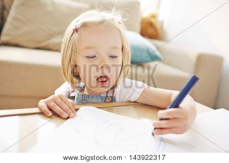 Closeup of cute blonde girl of five or six years busy doodling in living room, she is so concentrated on drawing that her mouth opens