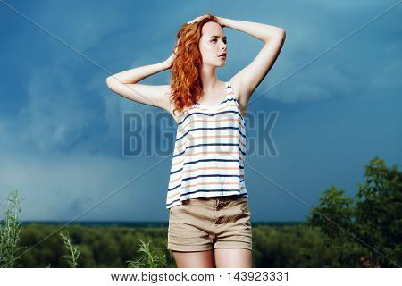 Portrait of a beautiful young woman on the background of a stormy sky.