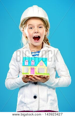Little girl in a builder helmet  holding house in her hands. The construction industry, mortgage concept. The house for the whole family.