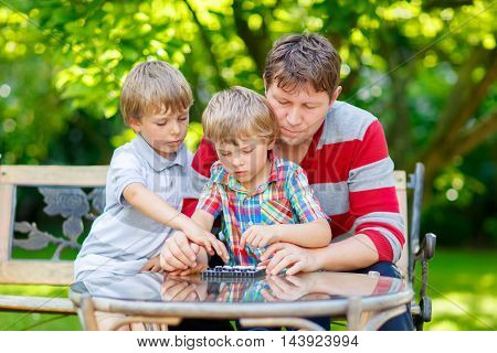 Two funny handsome kid boys and young father playing together checkers on board. Sons, siblings children and dad spending leisure together. Boys losing the game