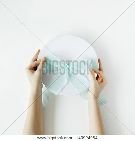 white gift cardboard box with blue bow and girl's hands on white background. flat lat top view