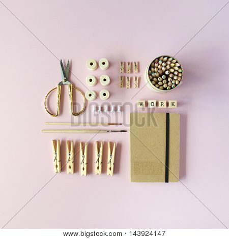 Flat lay top view brown eco style office table desk. feminine working supplies: craft diary pencil box brushes golden scissors spools pins on pink background.