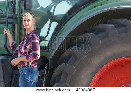 Female farmer and her tractor in summer