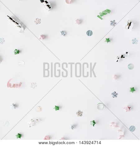 round frame with colored tinsel or frippery on white background. flat lay top view