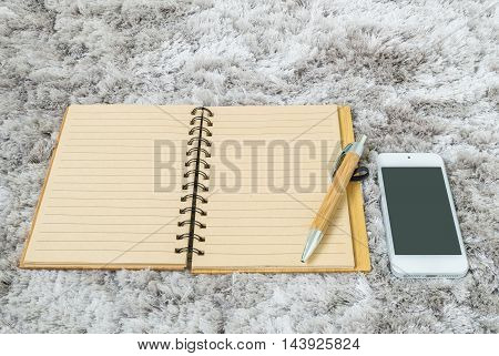 Closeup brown note book with line in page brown pen and smart phone on gray fabric capet textured background in top view in work concept