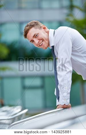 Young smiling attractive business man standing in the city