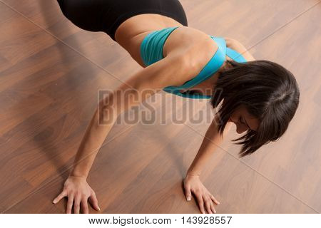 Portrait of a woman doing press-ups on the floor