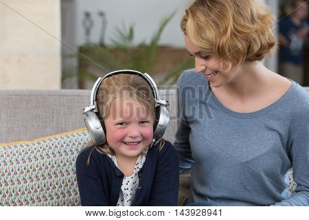 happy mom and daughter at home listening music