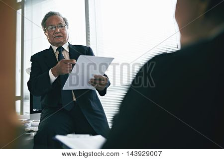 Senior Vietnamese lawyer consulting client in office