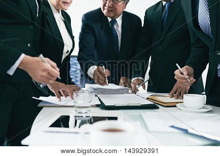 Hands of lawyers working with contracts and agreements