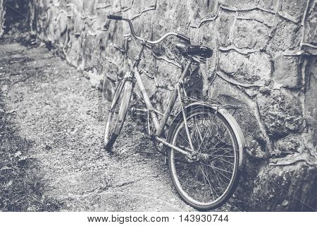 Vintage Bicycle Leaning against a brick Wall. Stylish retro photo.