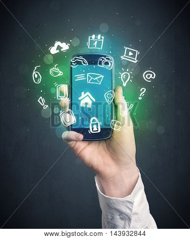 Caucasian hand in business suit holding a smartphone with drawn web icons