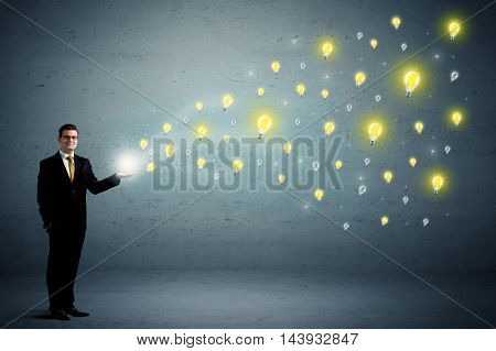 Caucasian businessman holding lightbulbs which are flying out from his hands