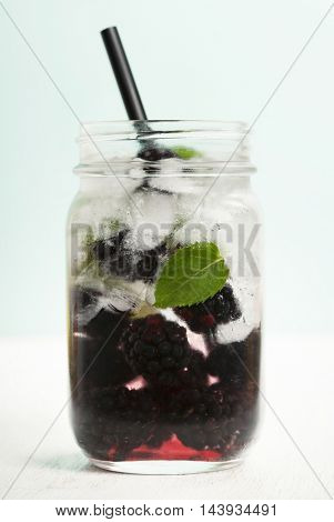 Infused water with fresh organic mulberry and mint on turquoise background