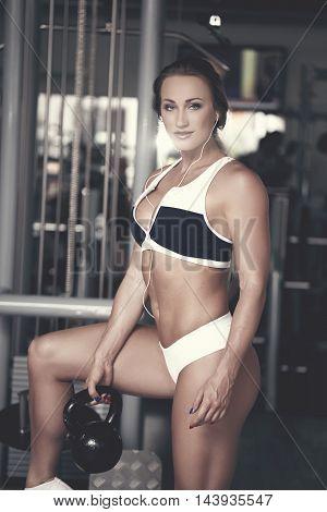 Fitness model holding kettlebell in gym retro style listening music