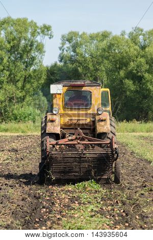The photo depicts a tractor digging potatoes