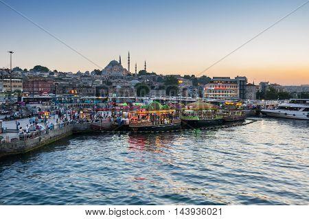 ISTANBUL TURKEY - JUNE 20 2015: Night view from Galata Bridge towards the Suleymaniye Mosque and fishing boats in Eminonu district Istanbul Turkey