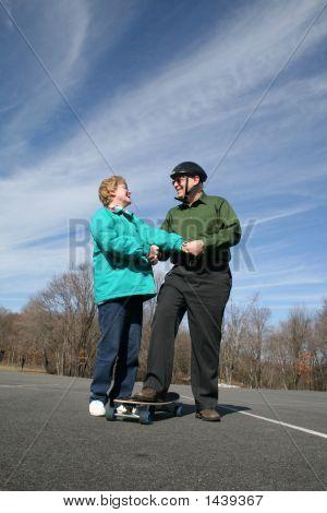 Senior Couple Holding Hands On Skateboarding Break!