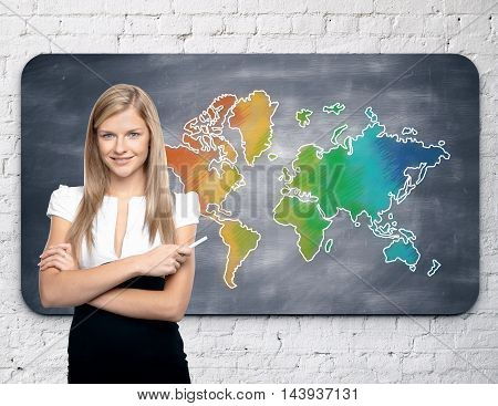 Businesswoman standing against chalkboard with colorful map hanging on white brick wall. Travel concept