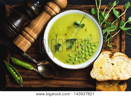 Fresh homemade pea cream soup in white bowl with grilled bread on wooden board over black backdrop, top view, horizontal composition