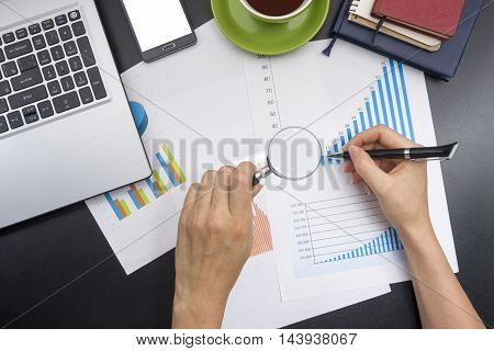 closeup of a young woman checking accounts. Office desk table with supplies top view.