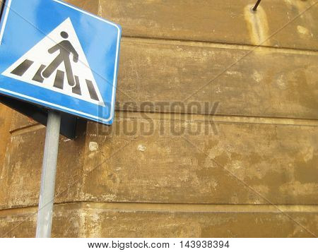 Pedestrian walk sign with empty copyspace brown wall background