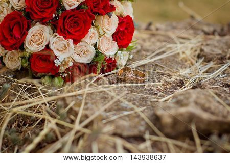 Wedding rings near bouquet of roses on the stone